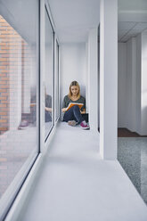 Student sitting at the window in hallway learning - ZEDF01027