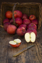 Red apples in basket, knife and halved on wood - LVF06428