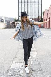 Fashionable young woman wearing hat balancing on rail - GIOF03524