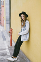 Portrait of fashionable young woman wearing hat leaning against facade - GIOF03527