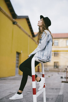 Fashionable young woman wearing hat sitting on railing - GIOF03530