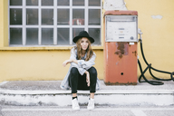 Portrait of fashionable young woman wearing hat sitting beside an old petrol pump - GIOF03533