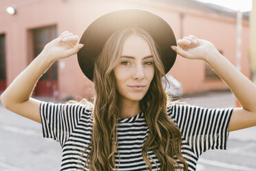 Portrait of fashionable young woman wearing hat - GIOF03539