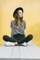 Portrait of fashionable young woman wearing hat sitting in front of yellow wall - GIOF03542