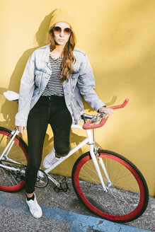 Portrait of fashionable young woman with bicycle - GIOF03545