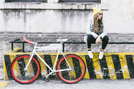 Fashionable young woman with bicycle sitting on railing - GIOF03548