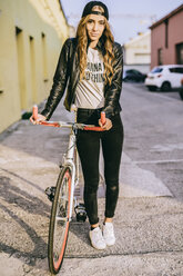 Portrait of fashionable young woman with bicycle - GIOF03554