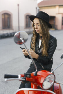 Portrait of fashionable young woman with red motor scooter using cell phone - GIOF03557