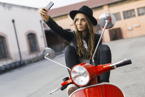 Portrait of fashionable young woman sitting on red motor scooter taking selfie with cell phone - GIOF03563