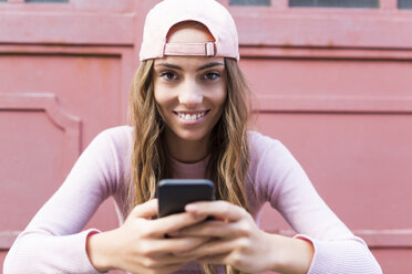 Portrait of fashionable young woman with cell phone wearing basecap - GIOF03566