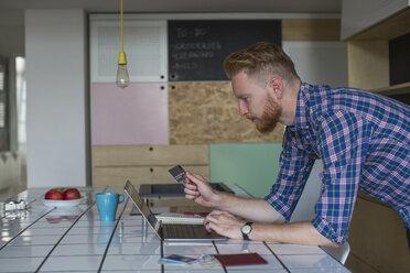 Man using credit card and laptop at home - MOMF00316
