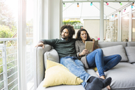 Couple sitting on couch reading book - MOEF00320
