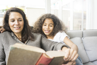 Mother and daughter sitting on couch reading a book - MOEF00323