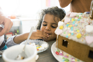 Little girl nibbling sweets for Christmas gingerbread house - MOEF00329