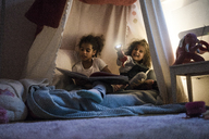 Two sisters sitting in dark children's room, playing with torch, reading book - MOEF00335