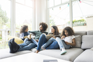 Happy family sitting on couch, reading books - MOEF00353