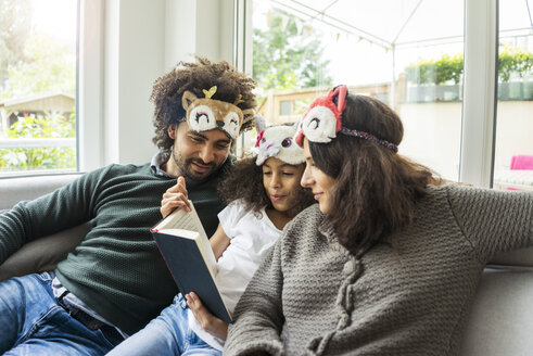 Happy family sitting on couch, wearing animal masks - MOEF00359