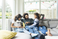 Happy family sitting on couch, daughter plaing with digital tablet - MOEF00362