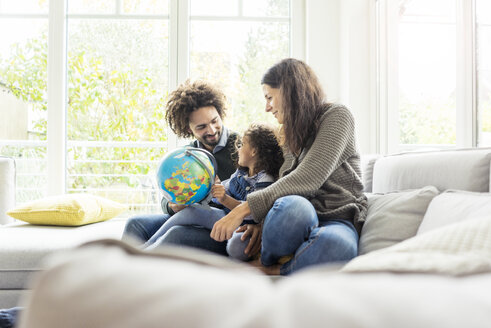 Happy family sitting on couch with globe, daughter learning geography - MOEF00365