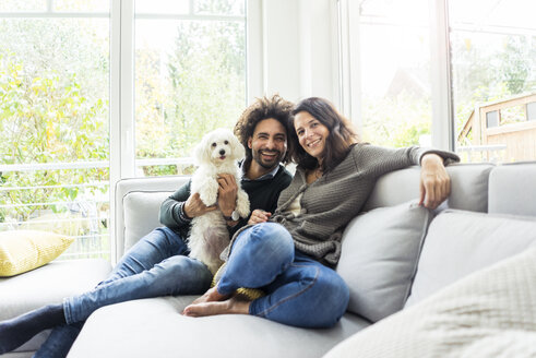 Happy family with dog sitting together in cozy living room - MOEF00368