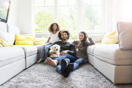 Happy family with dog sitting together in cozy living room - MOEF00371