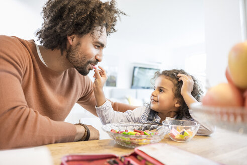Smiling girl feeding father at home with sweets - MOEF00377