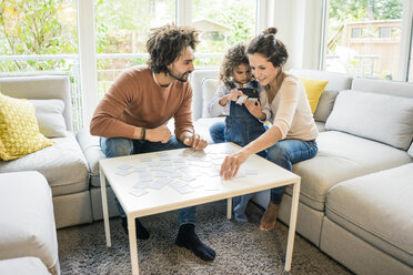 Family sitting on couch , playing memory game - MOEF00389