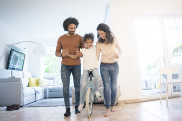 Parents helping daughter to ride a unicycle in the living room - MOEF00401