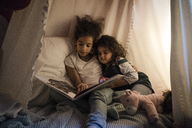Two sisters sitting in dark children's room, reading a book - MOEF00404