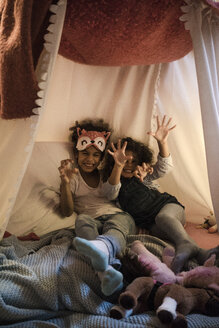 Sisters sitting on bed, playing wild animals - MOEF00407