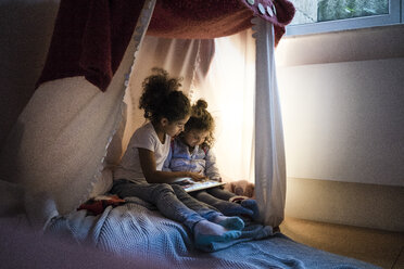 Two sisters sitting in dark children's room, looking at digital tablet - MOEF00410