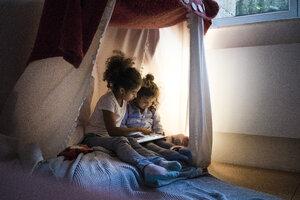 Two sisters sitting in dark children's room, looking at digital tablet - MOEF00410