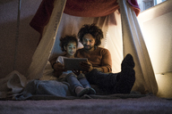 Father and daughter sitting in dark children's room, looking at digital tablet - MOEF00413