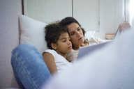 Mother and daughter lying in bed, reading children's book - MOEF00416