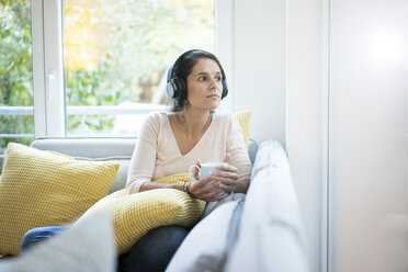 Woman sitting alone on couch, listening music with headphones - MOEF00419