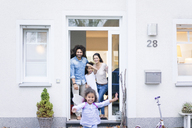 Laughing family waiting at the entrance of their home - MOEF00422