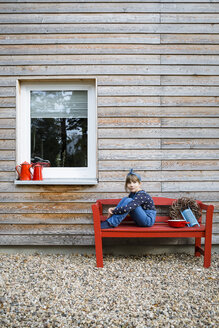 Girl sitting on red bench in front of a wooden facade - OJF00206