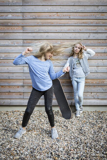 Two girls with skateboard in front of wooden facade - OJF00212