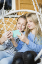Portrait of two girls relaxing in a hanging chair taking selfie with smartphone - OJF00221
