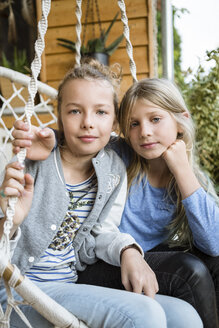 Portrait of two best friends sitting in a hanging chair on veranda - OJF00224