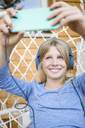 Portrait of laughing girl with headphones taking taking selfie with smartphone in a hanging chair - OJF00227