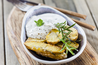 Bowl of potato wedges with rosemary and herbed curd cheese - SBDF03390