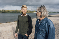 Father and son taking a stroll at Rhine river, meeting to talk - KNSF02871