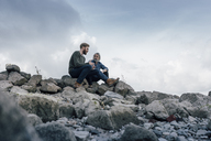 Father and son spending time together outdoors, taking a break, sitting on stones - KNSF02886