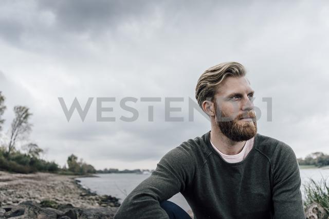 Young man sitting at the river in autumn, portrait - KNSF02901 - Kniel Synnatzschke/Westend61