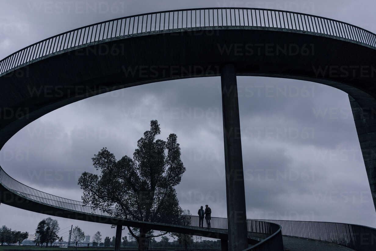 Two businessmen standing on dark bridge, having a meeting - KNSF02916 - Kniel Synnatzschke/Westend61