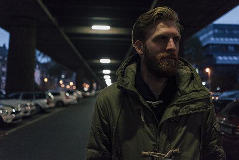 Young businessman walking under bridge at nicht - KNSF02922