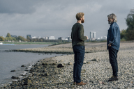 Father and son taking a stroll at Rhine river, meeting to talk - KNSF02931