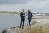 Father and son taking a stroll at Rhine river, meeting to talk - KNSF02934