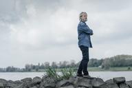 Senior man standing on stones looking at Rhine river - KNSF02940